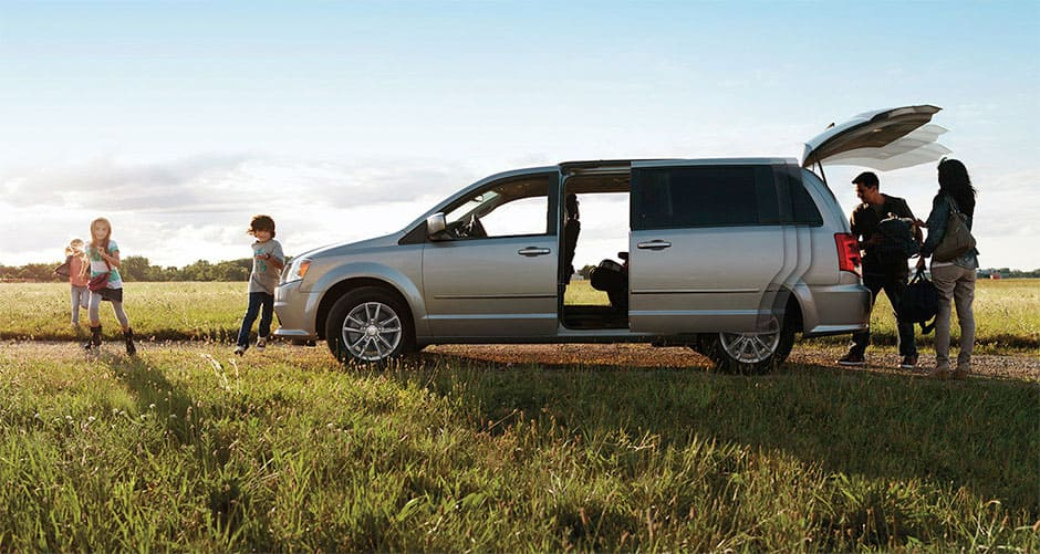 Family in Open Field Playing Around Dodge Grand Caravan