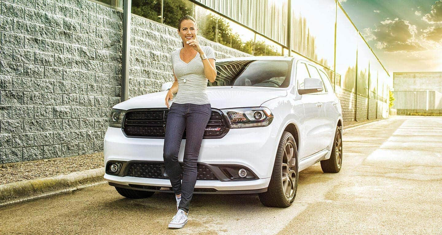 Display A woman posing in front of a 2020 Dodge Durango.
