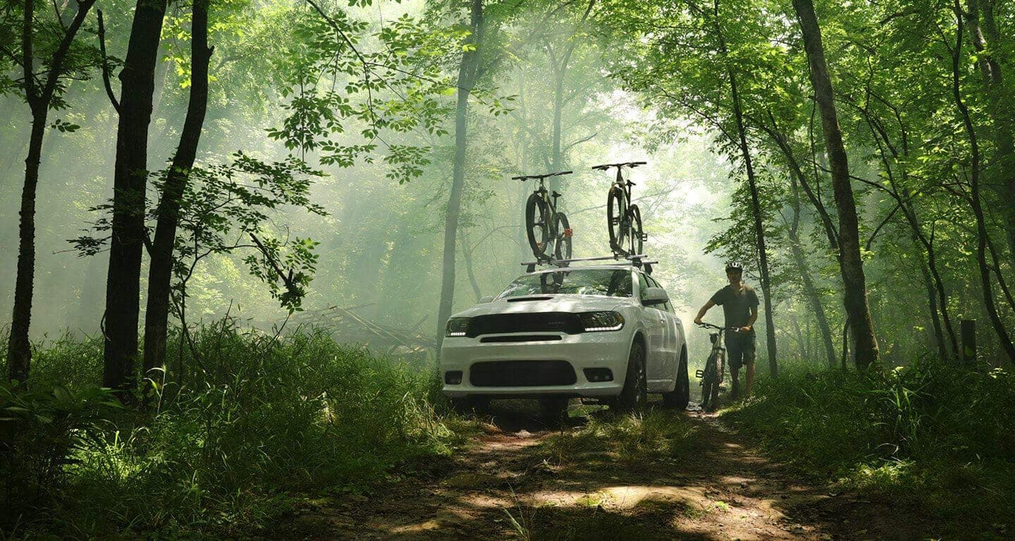 Display A three-quarter front view of a 2020 Dodge Durango, parked in the woods with two bicycles strapped to the roof rack.