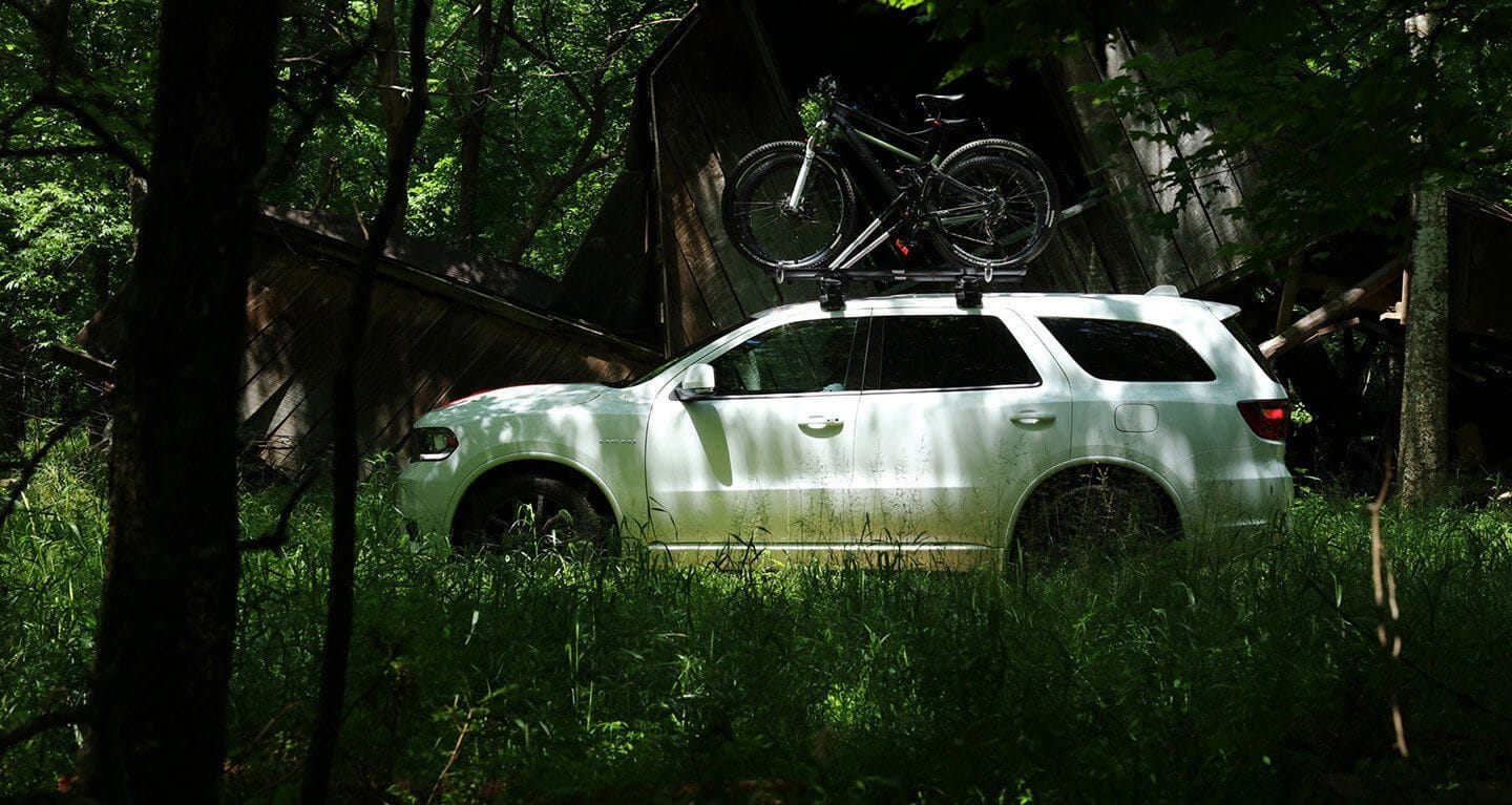 Display A profile view of a 2020 Dodge Durango parked in the woods with two bicycles strapped to the roof rack.