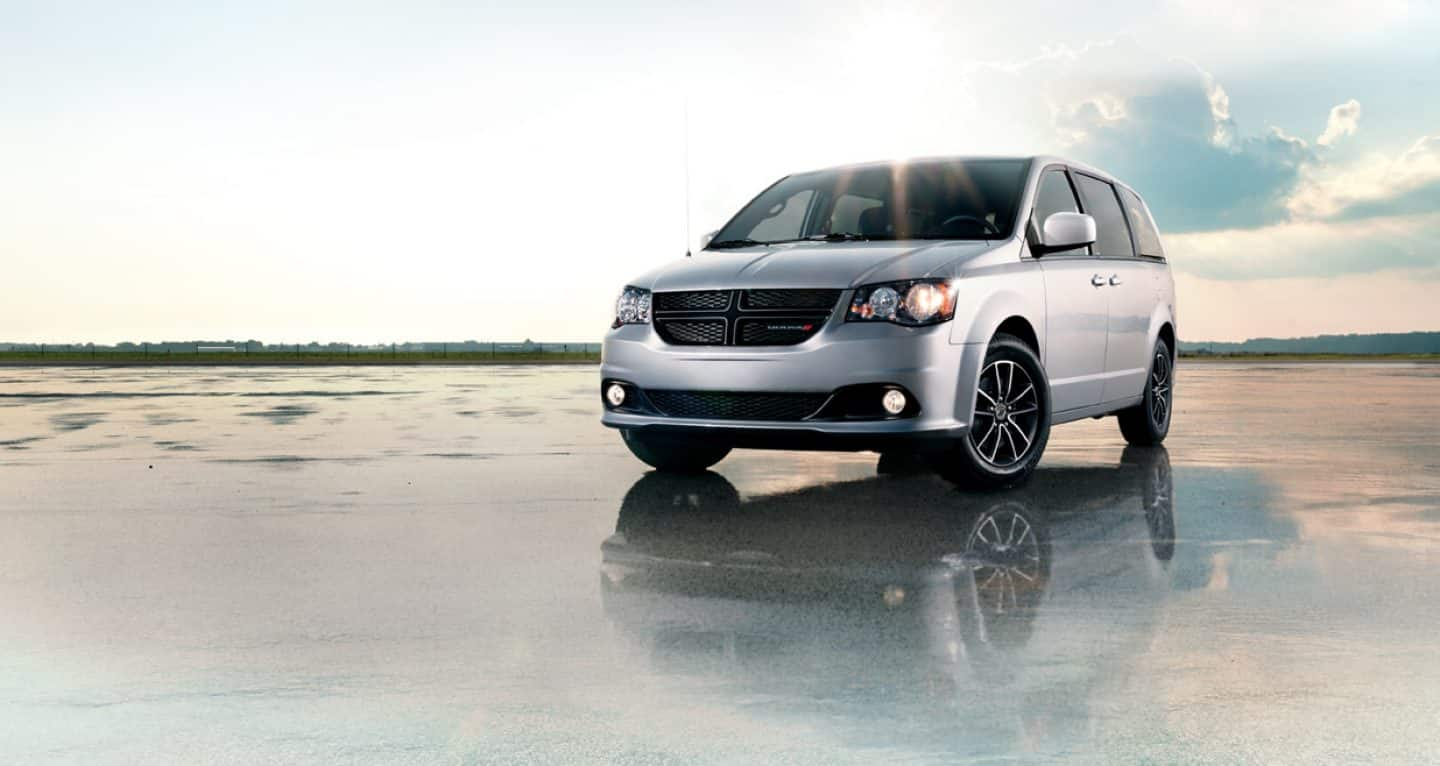 Display A three-quarter view of the 2019 Dodge Grand Caravan SXT on a beach.