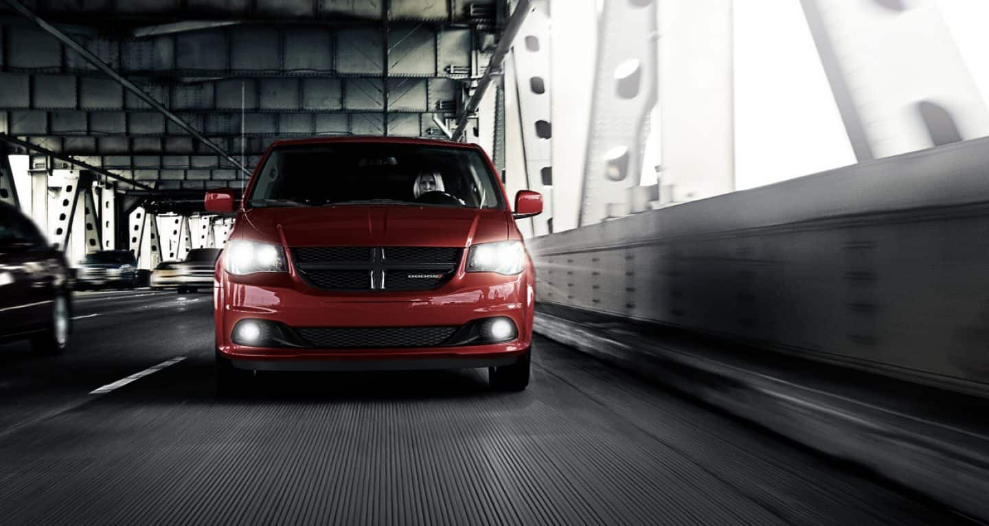 The Dodge Grand Caravan SXT with available Blacktop Package includes fog lamps and a black crosshair grille. Shown in Octane Red.