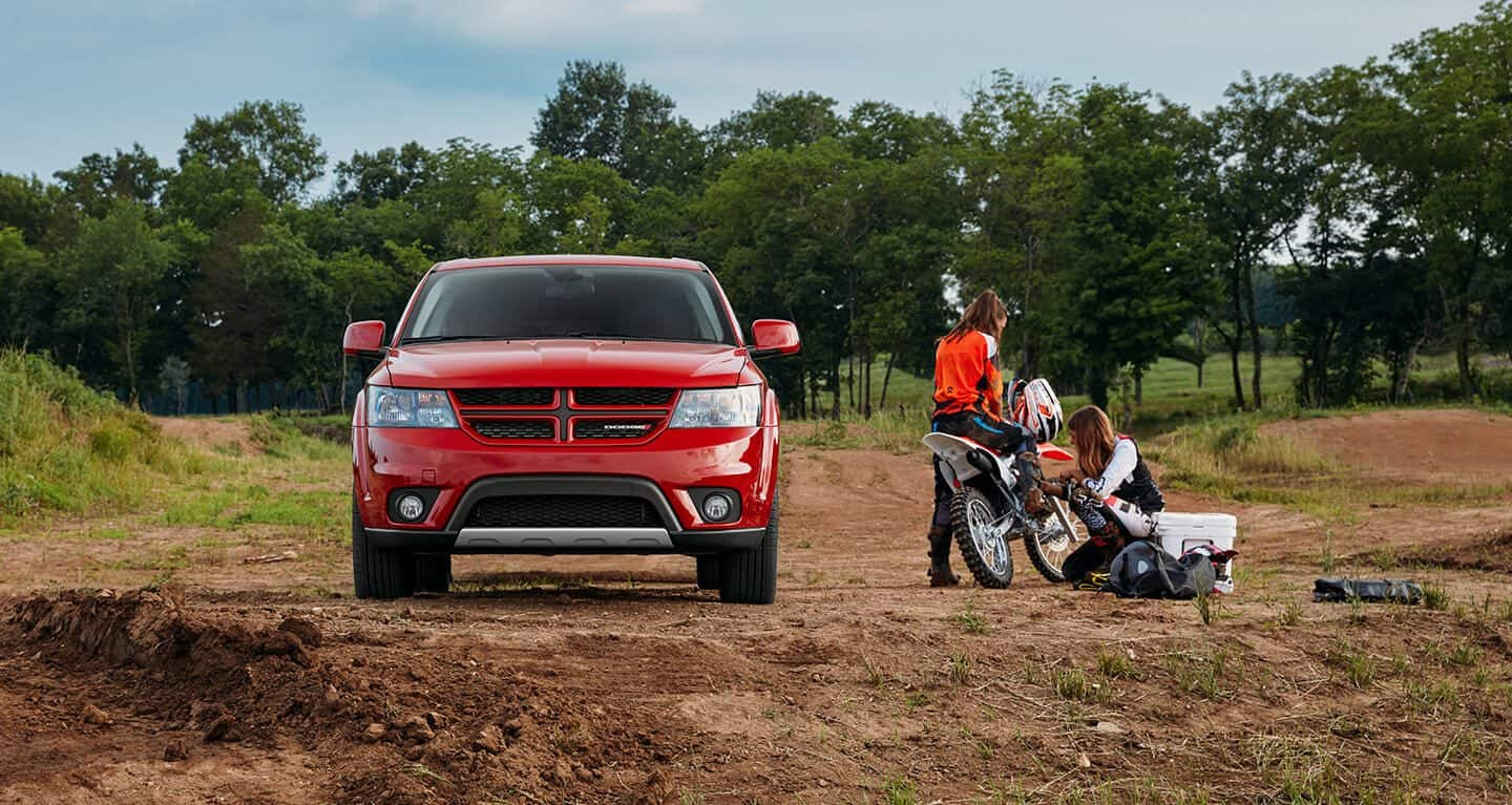 Display A head-on view of the 2019 Dodge Journey parked on a trail. Two women are working on a dirtbike next to it.
