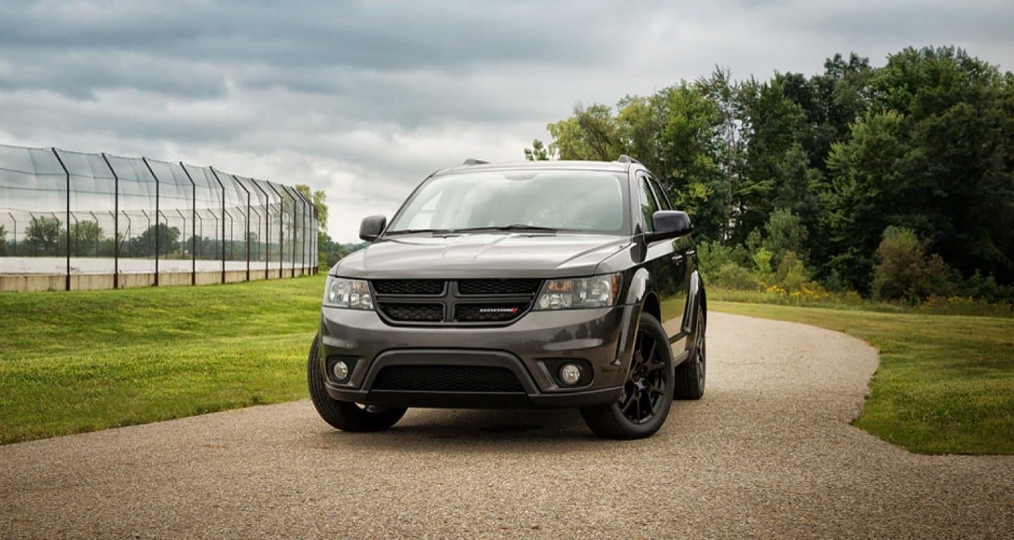 Display A 2019 Dodge Journey parked on a path beside an outdoor sports field.
