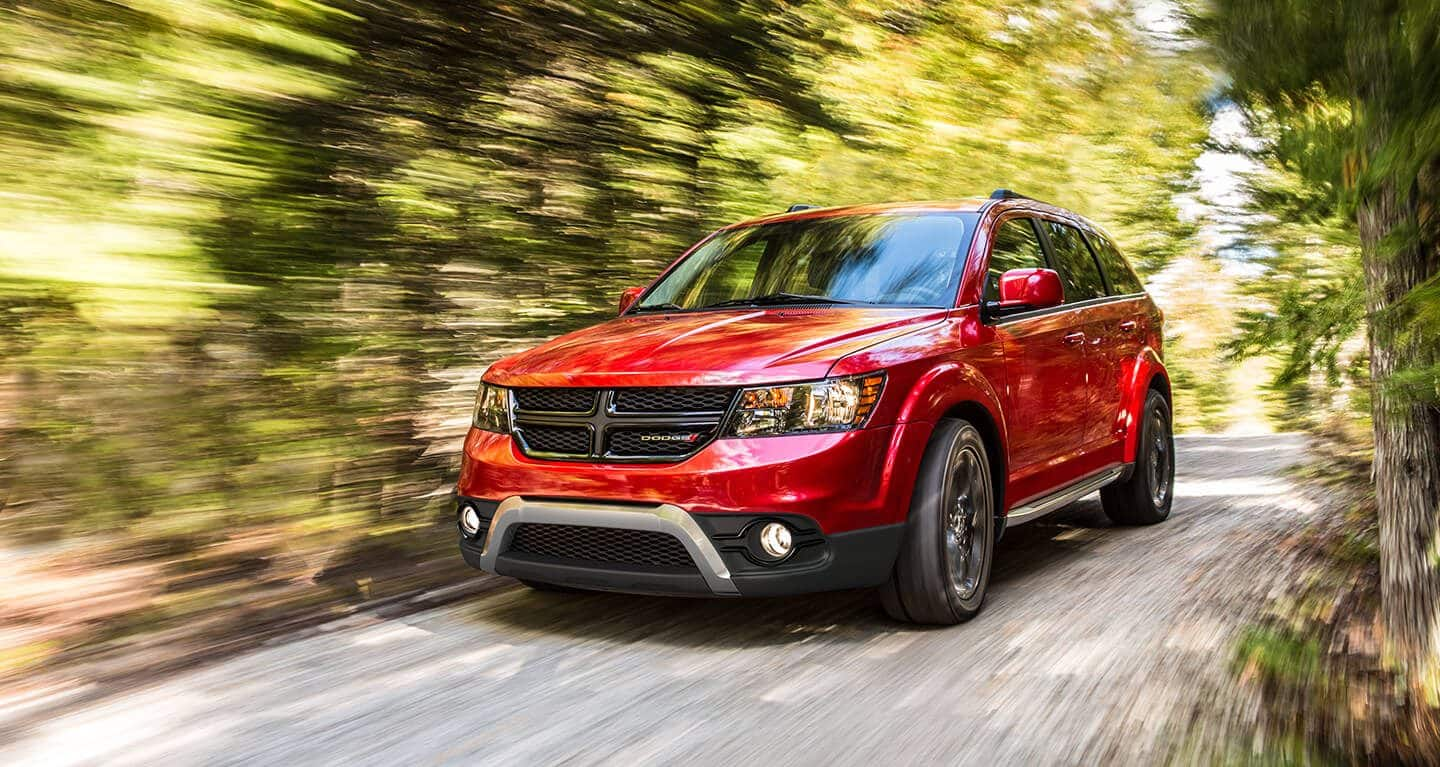 A three-quarter front profile of a 2020 Dodge Journey being driven through the woods.