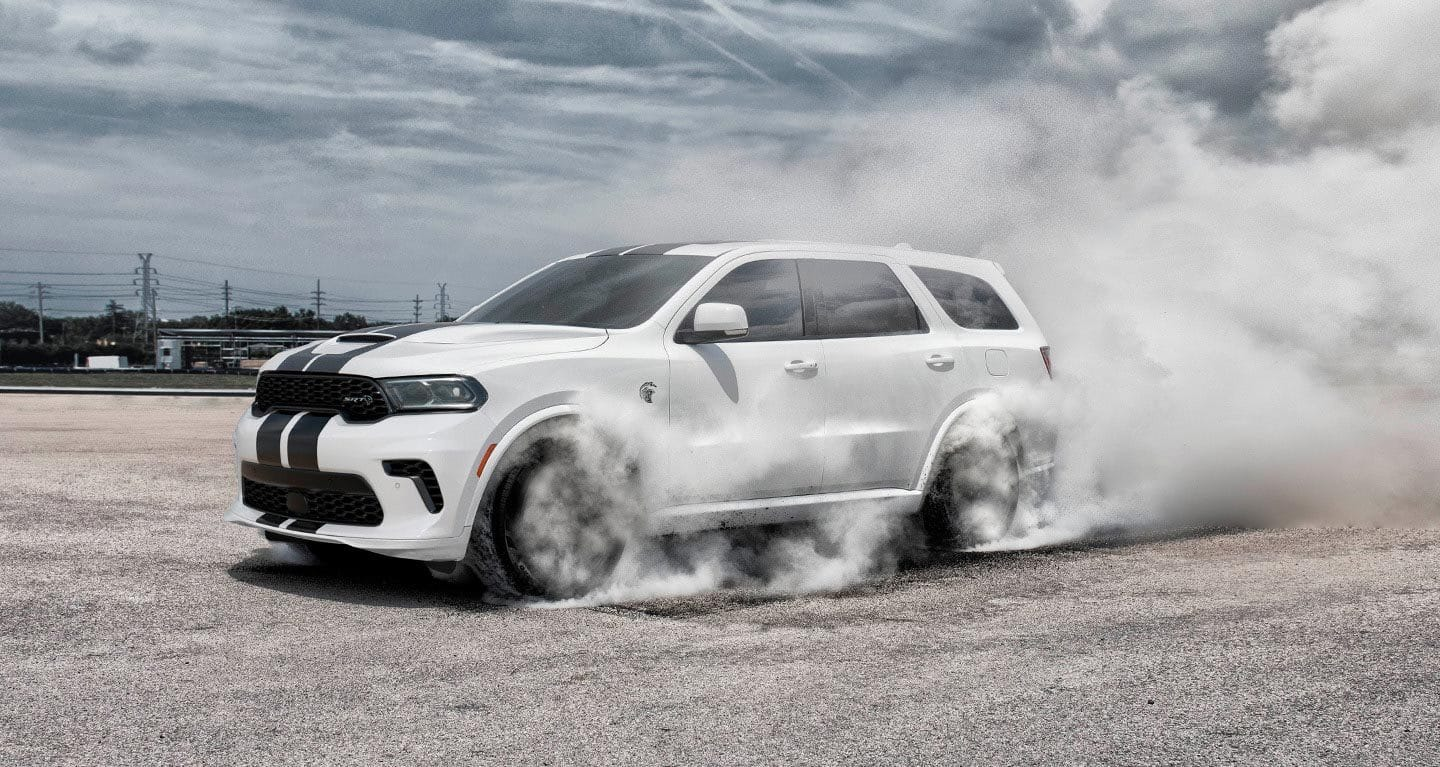 Display The 2021 Dodge Durango SRT Hellcat being driven on a track with a dust cloud behind it.