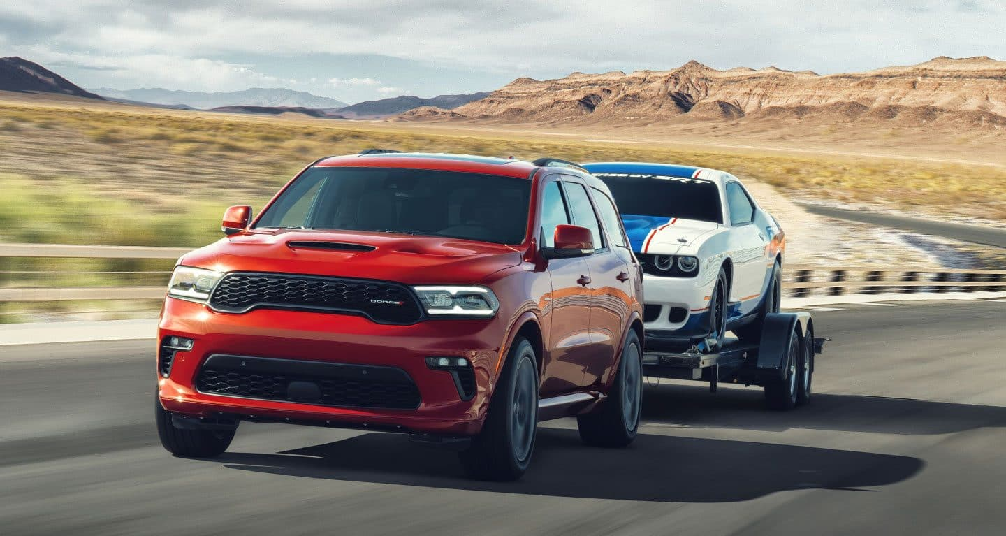 Display A red 2021 Dodge Durango R/T towing a Challenger on a flatbed trailer.