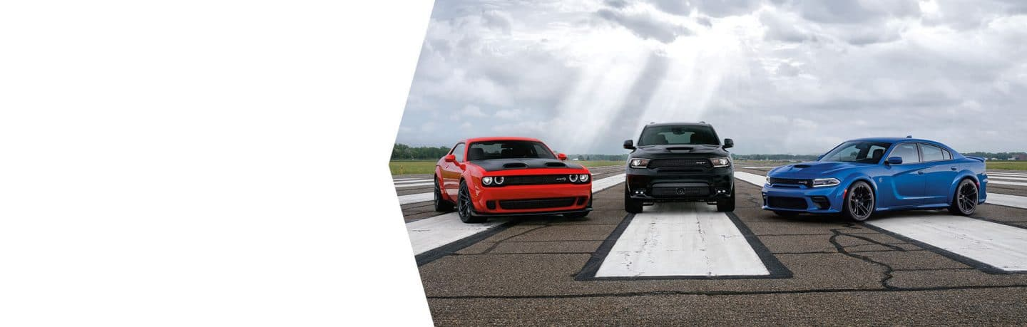 A 2020 Dodge Challenger SRT Hellcat Widebody, Durango SRT and Charger SRT Hellcat Widebody parked on an asphalt track.