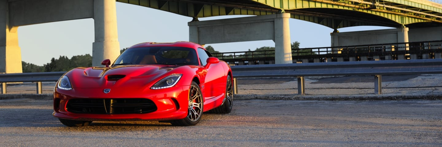 Three-quarter front profile view of a Dodge Viper parked on gravel under a bridge.